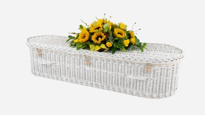 Child's willow coffin with a curved-end shape, painted white in colour and featuring painted white woven willow handles