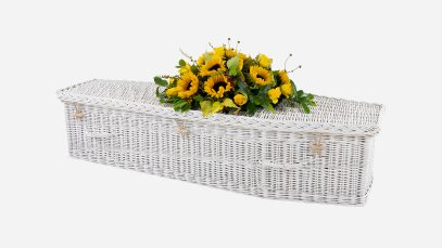 Child's willow coffin with a traditional shape, painted white in colour and featuring painted white woven willow handles
