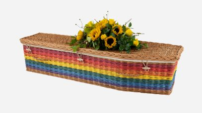 Child's willow coffin with a traditional shape in rainbow colours, featuring buff woven willow handles