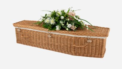 Child's willow coffin with a traditional shape, buff in colour and featuring buff woven willow handles